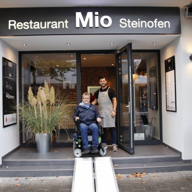 Frau Runte vom Behindertenbeirat der Stadt Gütersloh mit einem Vertreter des Restaurant Mio bei Übegabe der mobilen Rampe © Gütersloh Marketing